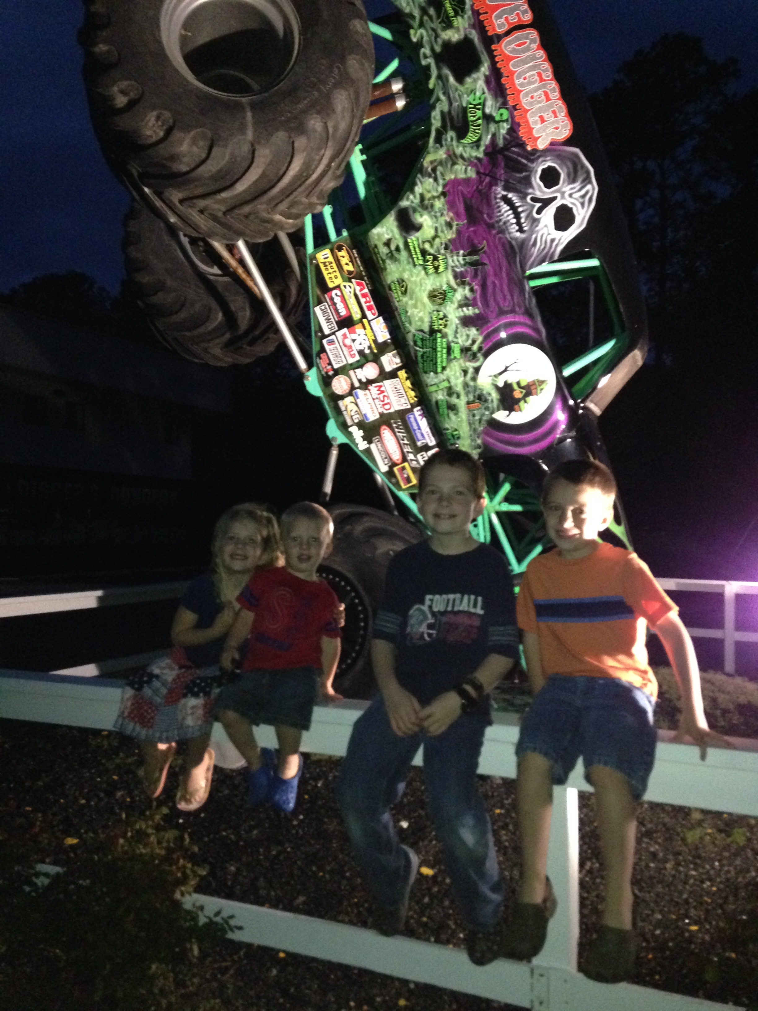 The kids sitting in front of another monster truck