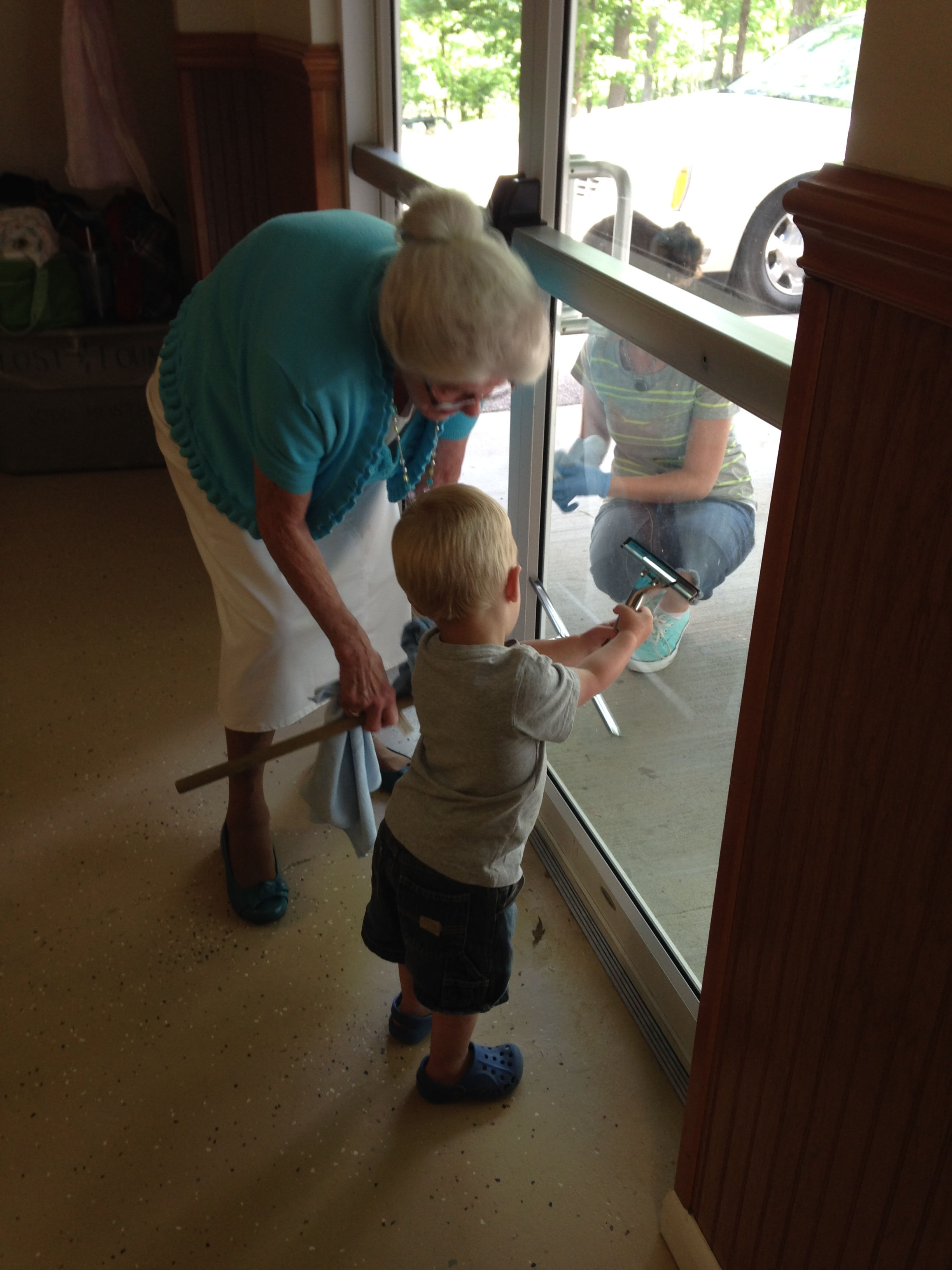 Kolby wanted to help Grandmommy clean the doors at the meeting hall.
