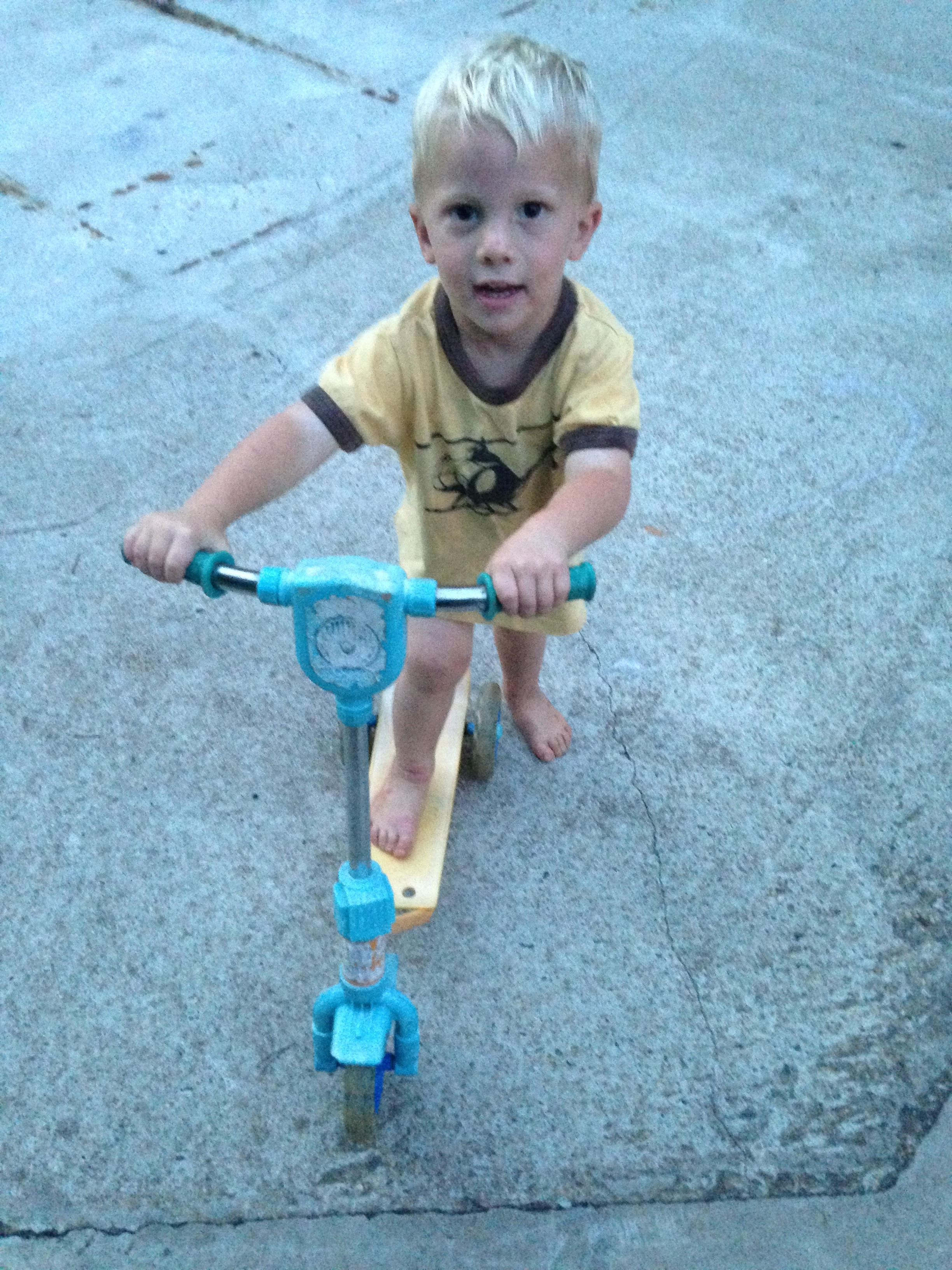Kolby inherited Kaylin's old scooter. He can truck around on it.