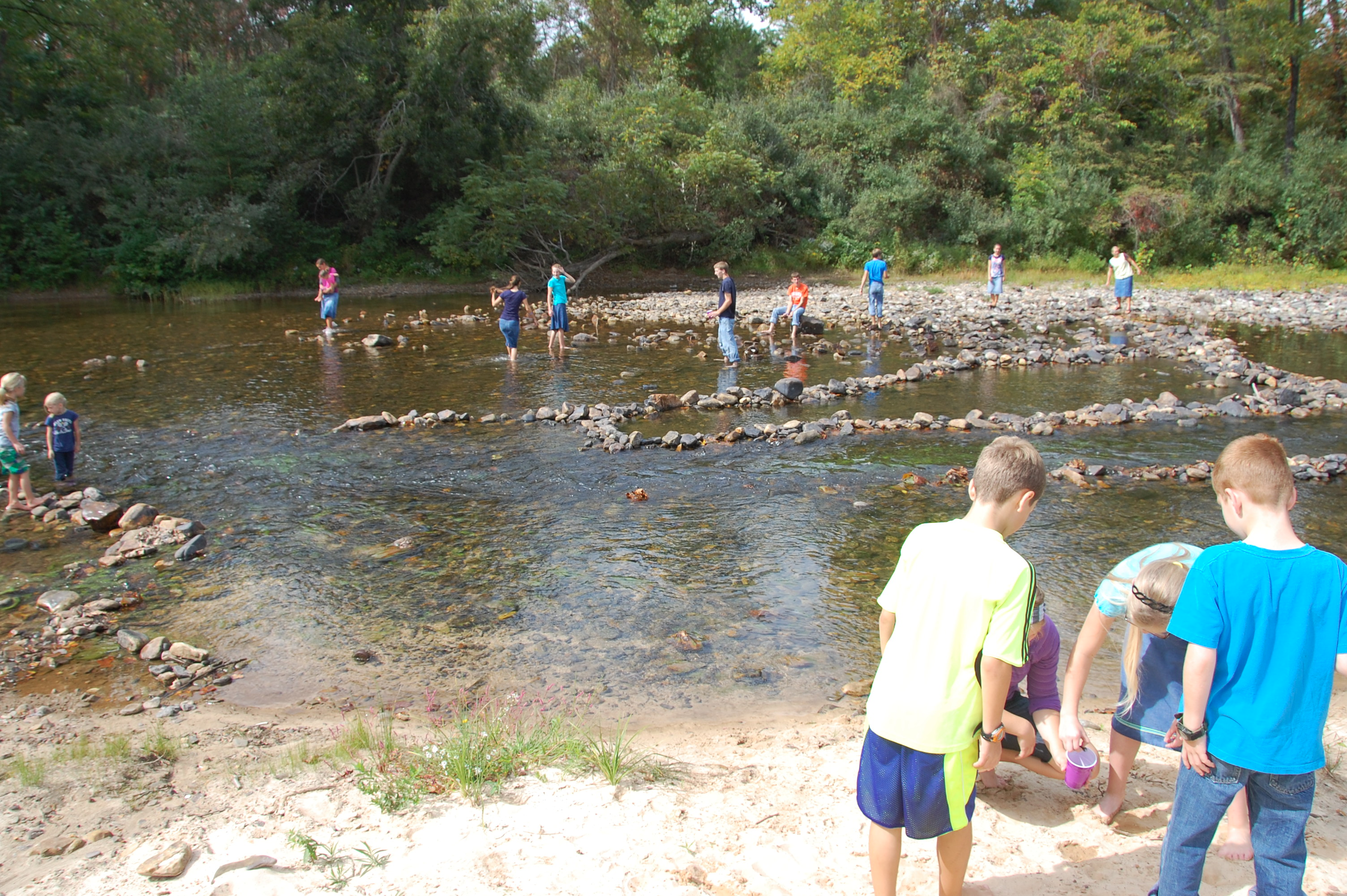 The young people were crawdad fishing in the river.